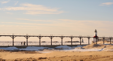 michigan snow: A winter beach is pictured with three unrecognizable people walking along a pier toward a lighthouse Stock Photo