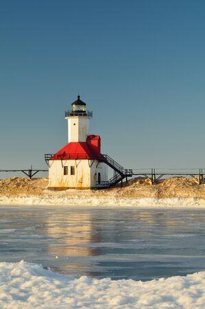 lake michigan lighthouse: Un faro se representa en invierno con nieve y un canal helado en primer plano Foto de archivo