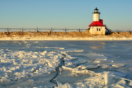 pictured: A lighthouse is pictured in winter with frozen and cracked ice in the foreground