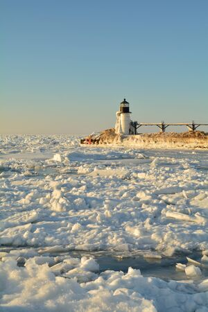 michigan snow: A lighthouse is pictured in winter surrounded by ice and snow.