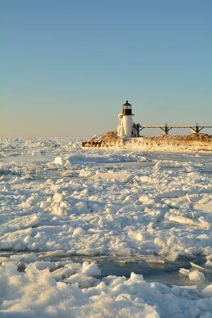 lake michigan lighthouse: Un faro se representa en invierno rodeado de hielo y nieve. Foto de archivo