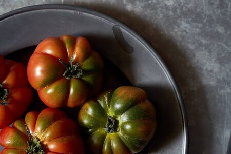 Tomatoes on a metal background Imagens