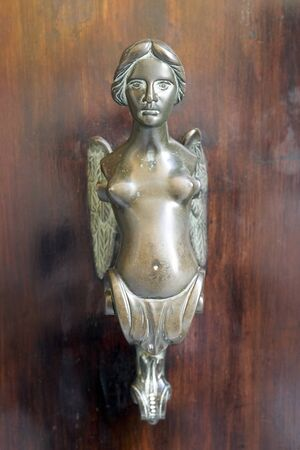 Detail of an ancient door. Bust of a woman with wings. Vertical