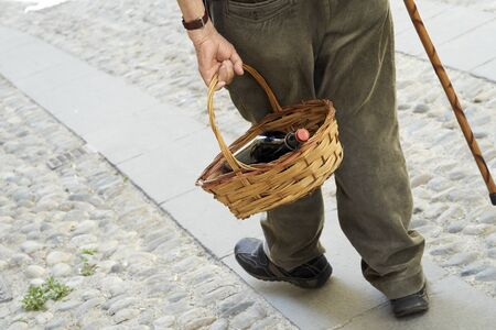 An elderly man walks with a basket in his hand containing a bottle of wine