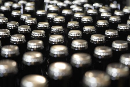 A close up of crown caps on beer bottles Imagens