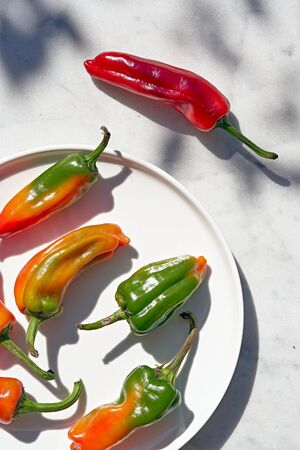 Yellow chili peppers, and a red chili pepper Imagens