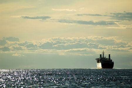 Huge boat sailing in the late afternoon sea with cloudy sky in the background Stock Photo