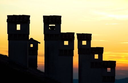 Seven chimneys and a sunset yellow  orange sky in the background