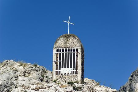 cristian: Small chapel on the stony hill with clear blue sky in the background