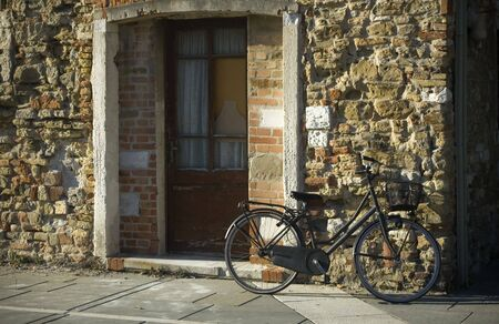 Bicycle parked by the old house made of stone