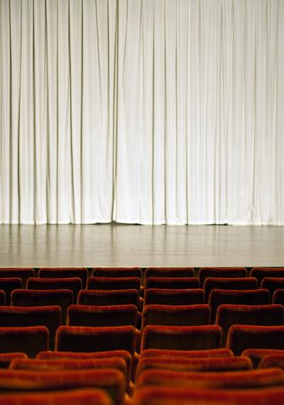 Theater stage with white curtain in the background and red seats in the front