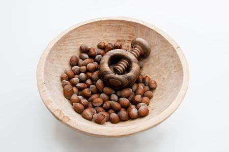 Wooden bowl filled with hazelnuts, walnuts and nut crasher.