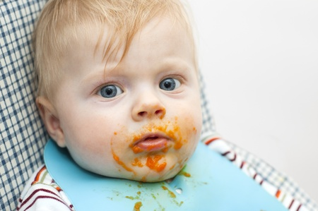 Little kid dirty with food on the face looking straight into the camera photo