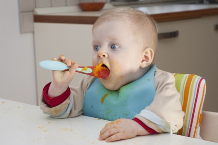 Little kid dirty on face by the food, feeding himself with the spoon