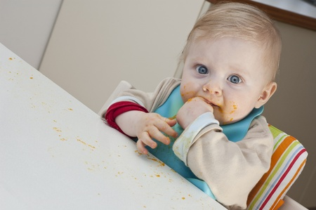 Little kid dirty with food on the face looking straight into the camera Stock Photo