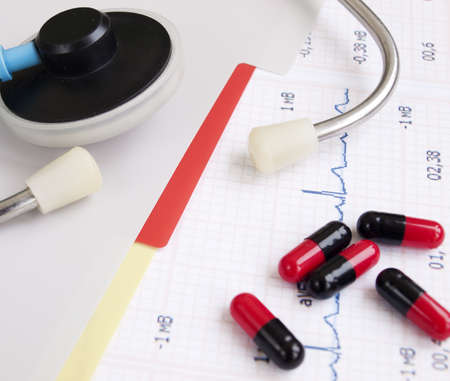 heartrate: Stethoscope and pills on a printout of a heartrate graph Stock Photo