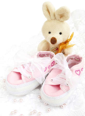 Pair of pink  Babies shoes with toy and pearls photo