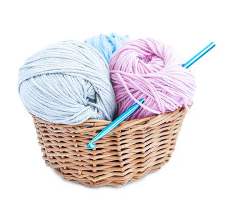 Cesta con aguja de crochet y hilo sobre un fondo blanco