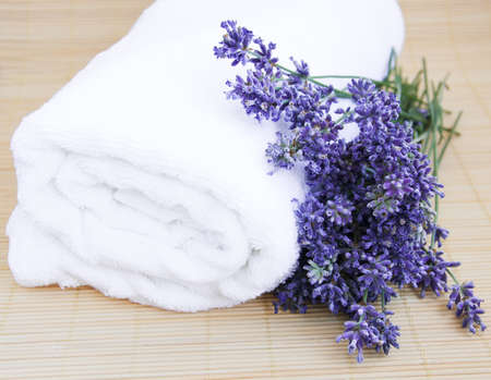 lavender bunch with  white towel on a bamboo rug photo