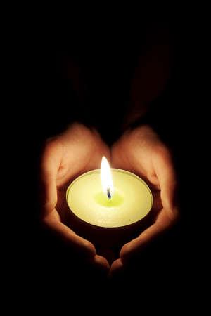 Hands holding one candle in darkness photo