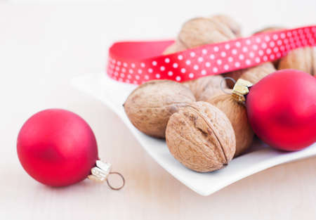Christmas still life with  walnuts, ribbon and red balls. photo