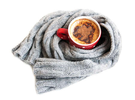 Cup of cocoa wrapped in grey scarf on a white background photo
