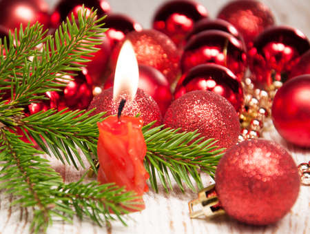 Red burning candle,  christmas baubles and tree photo