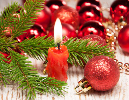 Red burning candle,  christmas baubles and tree Stock Photo - 16650146