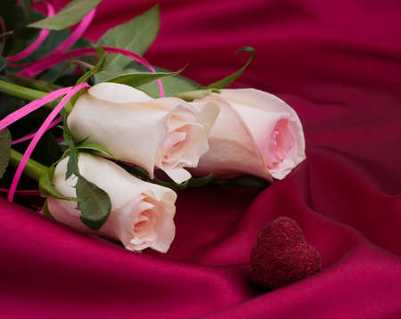 Pink Roses on a romantic red satin background photo