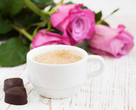 Cup of coffee with heart shape candy  and bunch of  roses. photo