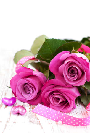 Pink Roses and hearts on a wooden background photo