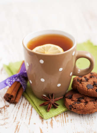 Cup of tea with lemon and chocolate cookies photo