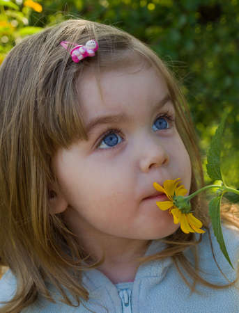 Little girl smelling flower Stock Photo