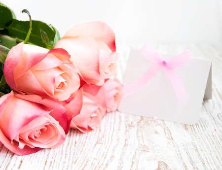 Blank-Karte für Ihre Nachricht und rosa Rosen auf einem hölzernen Hintergrund