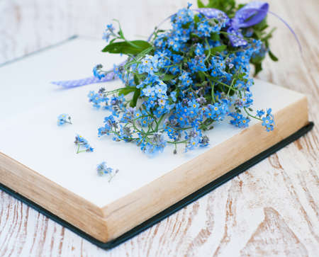 Forget me not flowers and old book