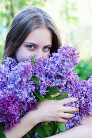 Beautiful girl holding a lilac spring  flowers photo