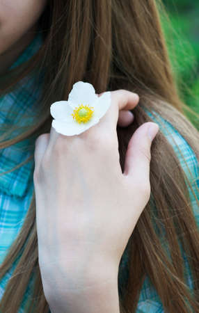 La mano de una chica con la flor blanca del resorte photo