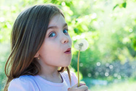 A little girl making a wish on a dandelion photo