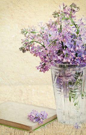 Bouquet von lila in einer Vase und alte Buch auf einem Grunge-Hintergrund
