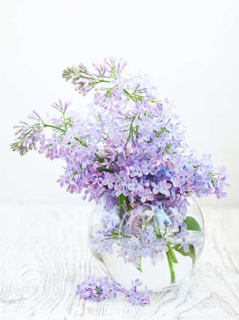 Bouquet of a lilac in a  vase  on a wooden  background photo