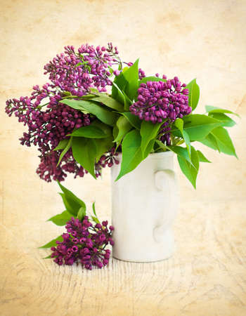 Bouquet of a lilac in a white vase on a grunge  background photo