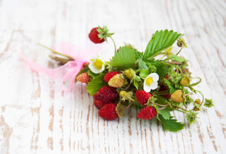 wild strawberry: bunch of  wild strawberry on a wooden background Stock Photo