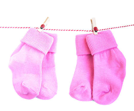 pink socks for baby girl hanging on rope, isolated