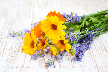 bouquet of calendula and lavender  flowers on a wooden background