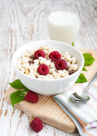 Fresh morning bowl of muesli and raspberries with milk photo