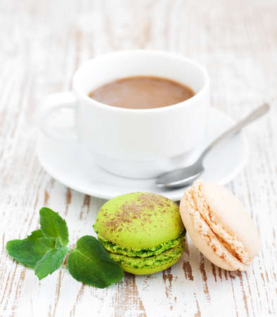 Assorted Macaroons with coffee  and mint leaves photo