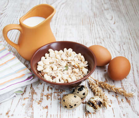 Müsli, Weizen, Milch und Eier auf einem hölzernen Hintergrund