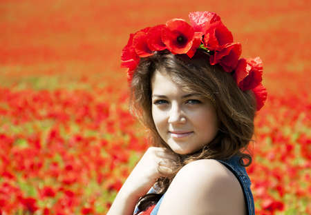 Young beautiful girl  on the poppy flowers photo