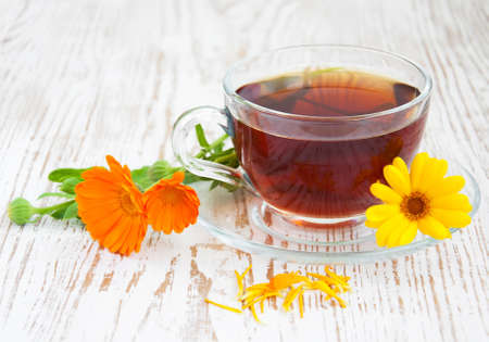 Tea cup with calendula flowers on a wooden background photo