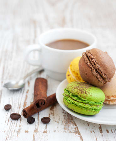 Assorted Macaroons with coffee  and cinnamone sticks photo